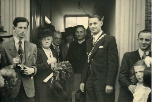 Burgemeester Jan Meuwese tijdens zijn installatie op 22 juni 1946 voor de ingang van het oude gemeentehuis. Links zijn moeder. Rechts staat Leo Tooten.
